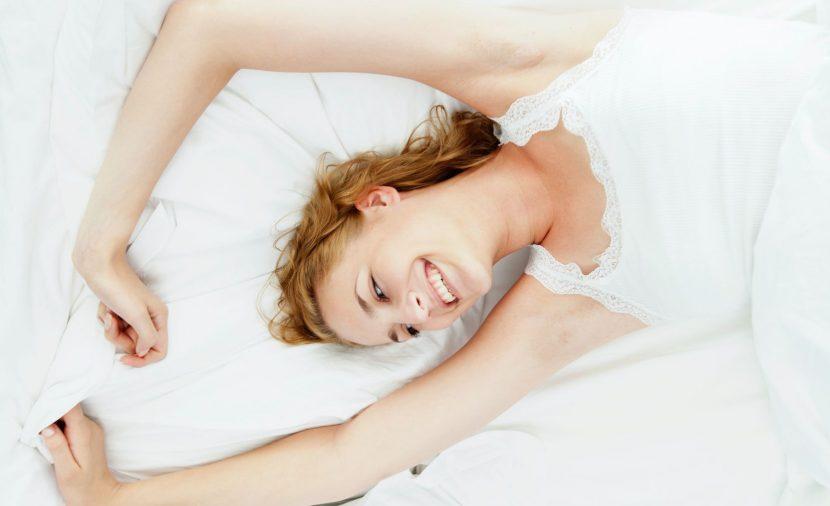Femme dans son lit qui s'étire